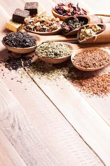 Diverse gedroogde thee in houten lepels en lepels met kopieerruimte