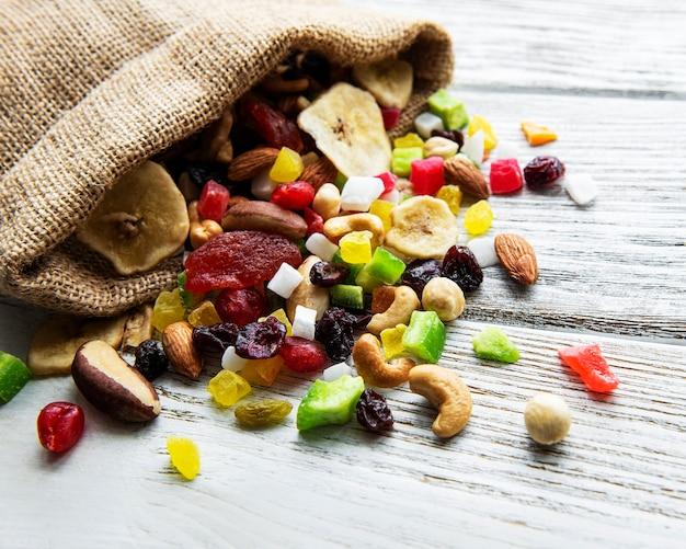 Diverse gedroogde vruchten en meng noten op een witte houten achtergrond.