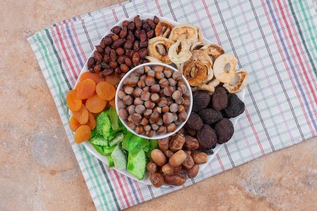 Diverse gedroogde vruchten en noten op een witte plaat.