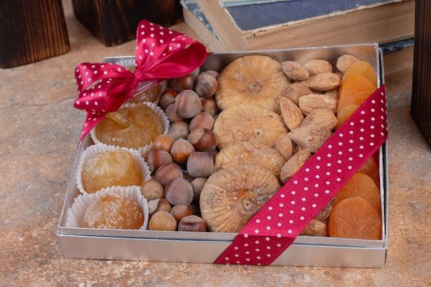 Diverse gedroogde vruchten en noten op geschenkdoos.