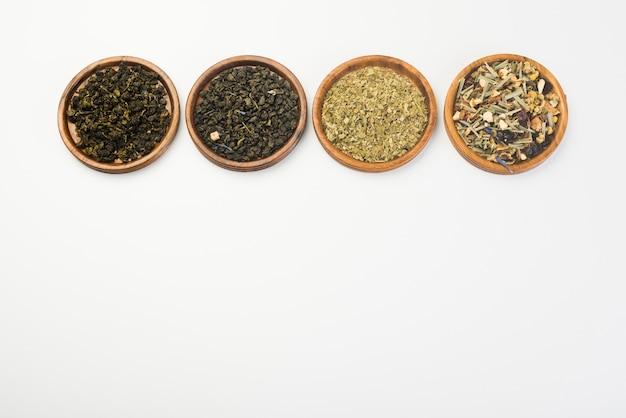 Diverse gedroogde weide kruiden thee op houten ronde plaat tegen witte achtergrond