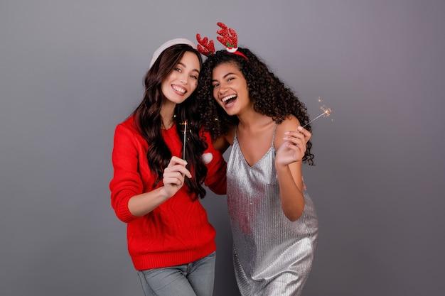Diverse gelukkige vrouwen met fonkelende sterretjes die kerstmishoed dragen die over grijs wordt geïsoleerd