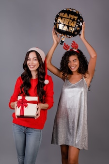Diverse gelukkige vrouwen met giftdoos en gelukkige nieuwe jaarballon die kerstmishoed dragen die over grijs wordt geïsoleerd