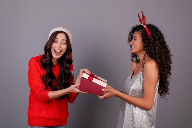 Diverse gelukkige vrouwen met giftdoos met lint die kerstmishoed dragen die over grijs wordt geïsoleerd
