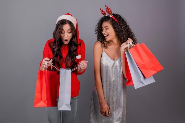 Diverse gelukkige vrouwen met kleurrijke het winkelen zakken die rode santahoed dragen die over grijs wordt geïsoleerd