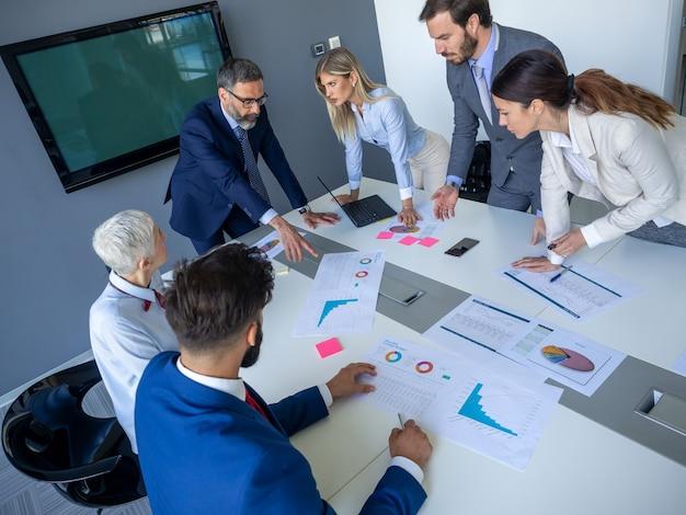 Diverse gelukkige zakenmensen in bestuurskamervergadering, werken op kantoor.