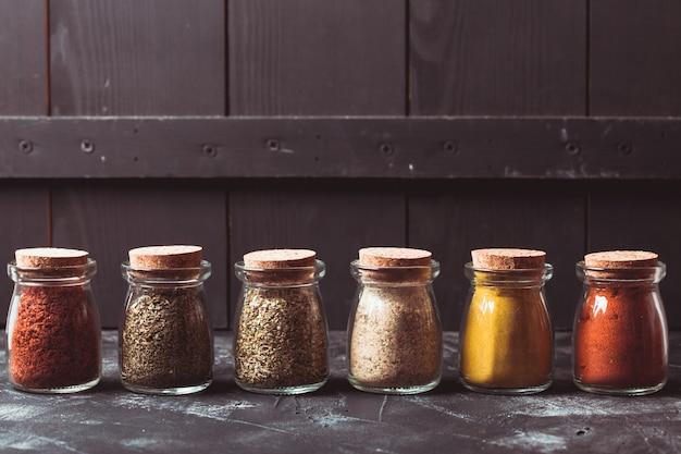 Diverse gemalen kruiden in vintage glazen flessen