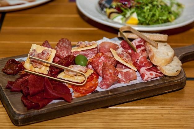 Diverse gerechten en snacks van vlees op de feesttafel.