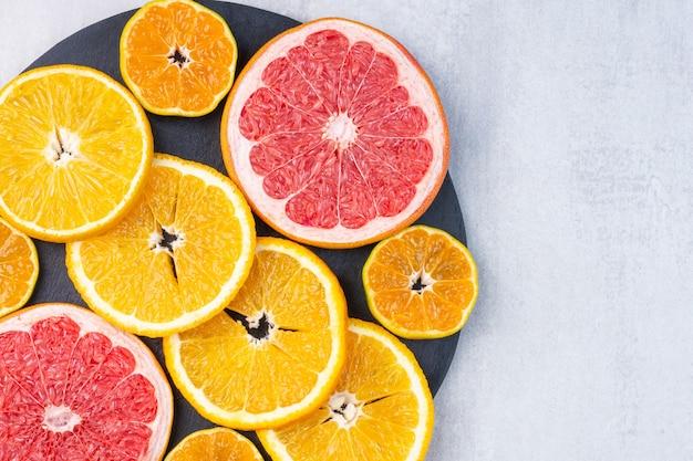 Diverse gesneden fruit op een bord, op het marmer.