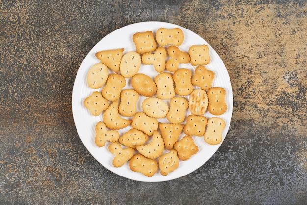 Diverse gezouten crackers op witte plaat.