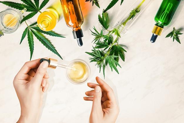 Diverse glazen flesjes met cbd-olie, thc-tinctuur en hennepbladeren. cosmetica cbd-olie. vrouwelijke handen met een pipet met cosmetische cbd-olie