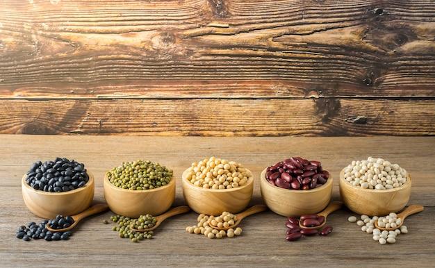 Diverse granen zoals sojabonen zwarte bonen rode bonen gedroogde maïs in een houten kopje op een houten tafel