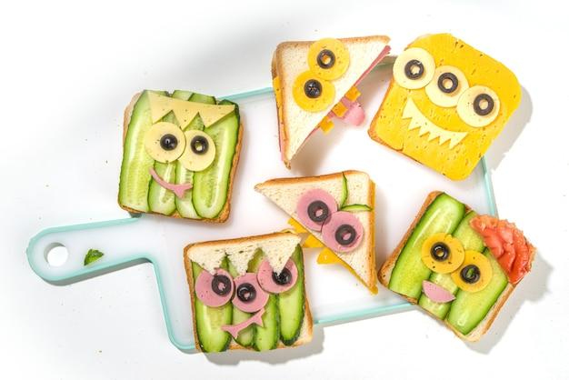 Diverse grappige monster halloween sandwiches. stel assortiment creatieve ontbijtsnacktoosts in met kaas, halloween-kinderfeestvoedsel, bovenaanzicht