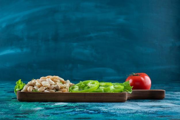 Diverse groenten en bonen op een bord op de blauwe tafel.