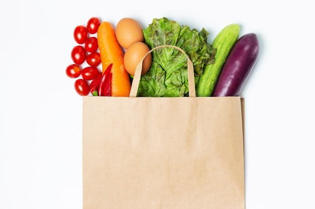 Diverse groenten en fruit in een papieren zak op een wit oppervlak