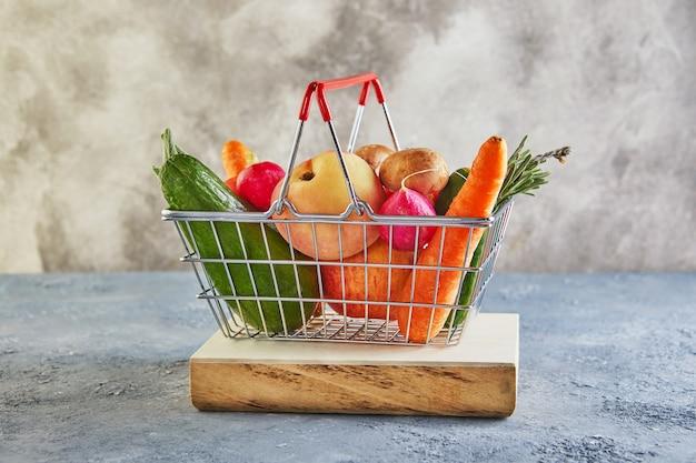 Diverse groenten en fruit liggend in de mand van een supermarkt op een houten podium