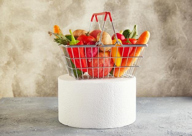 Diverse groenten en fruit liggend in de mand van een supermarkt op een wit podium