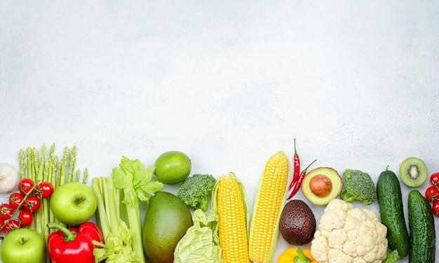 Diverse groenten en fruit op een rij op lichtgrijze betonnen ondergrond