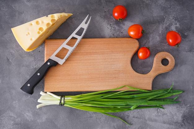 Diverse groenten en houten snijplank op een grijze achtergrond, plaats voor tekst. bovenaanzicht.