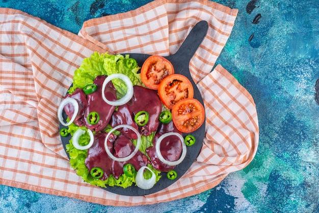 Diverse groenten en kippenlevertjes gesneden op de snijplank op de theedoek