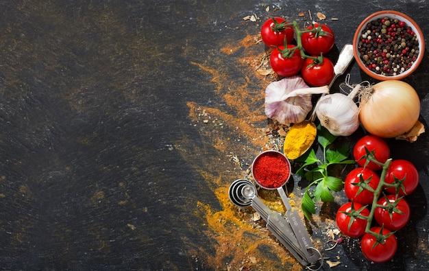 Diverse groenten en kruiden voor het koken op donkere achtergrond, bovenaanzicht