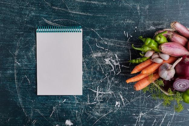 Diverse groenten geïsoleerd op blauwe tafel aan de rechterkant met een receptenboek opzij.