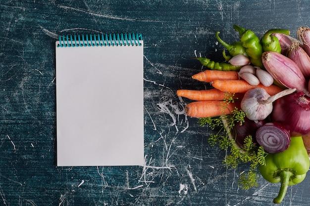 Diverse groenten geïsoleerd op blauwe tafel met een receptenboek opzij.