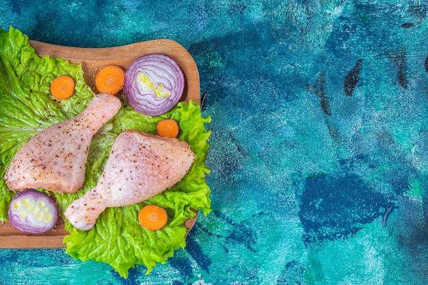 Diverse groenten gesneden en gemarineerde kipdrumsticks op de snijplank
