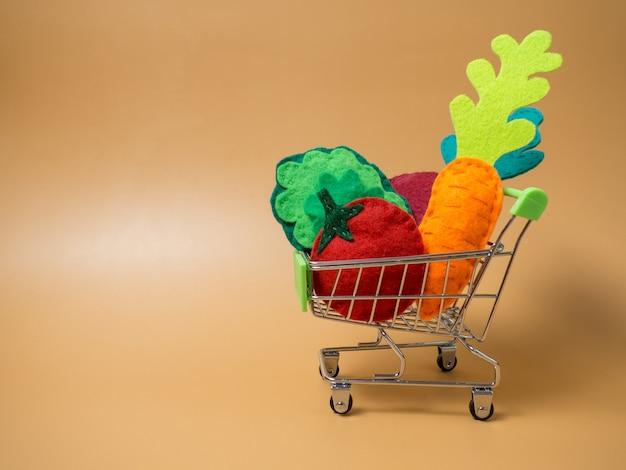 Diverse groenten in een karretje van een supermarkt op een oranje achtergrond, groenten van vilt