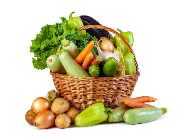 Diverse groenten in een rieten mand isoleren op wit, vers voedsel