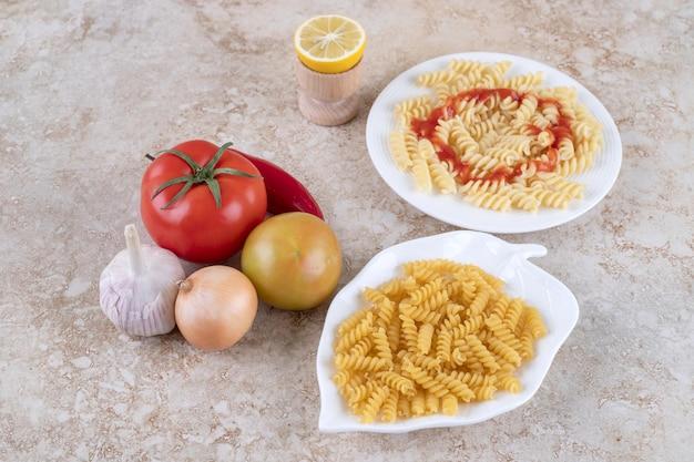 Diverse groenten naast macaronischotels op marmeren oppervlakte
