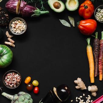 Diverse groenten op zwarte achtergrond met exemplaarruimte voor tekst