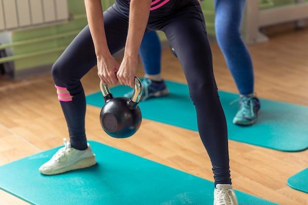 Diverse groep die mensen opleiding met kettlebells in industriële gymnastiek uitwerkt