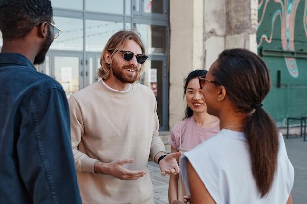 Diverse groep hedendaagse jongeren die buiten kletsen in de stedelijke omgeving, focus op lachende man met zonnebril
