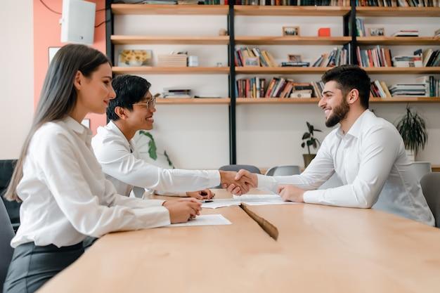 Diverse groep jonge bedrijfsmensen die en aan handen op een overeenkomst in het bureau samenwerken schudden