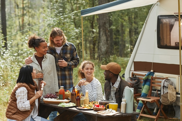 Diverse groep jonge mensen genieten van picknick buiten tijdens het kamperen met aanhangwagen