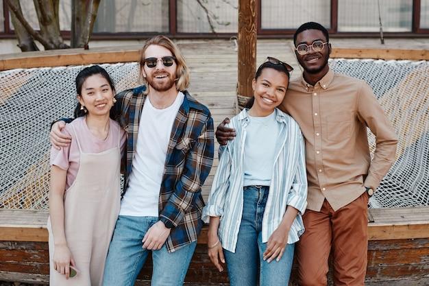 Diverse groep jonge mensen poseren buiten in de stedelijke omgeving en glimlachen naar de camera