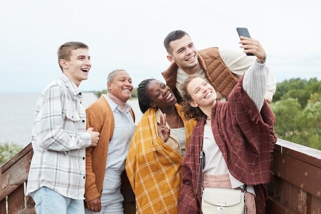 Diverse groep jonge vrienden die selfie nemen op gezichtspunt tijdens wandeling kopieerruimte