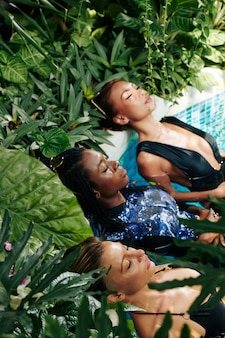 Diverse groep jonge vrouwen in zwemkleding ontspannen in het buitenzwembad met borrelend water