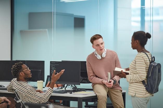 Diverse groep jongeren die project bespreken terwijl ze samenwerken in het it-lab op kantoor of op school met computers, kopieer ruimte