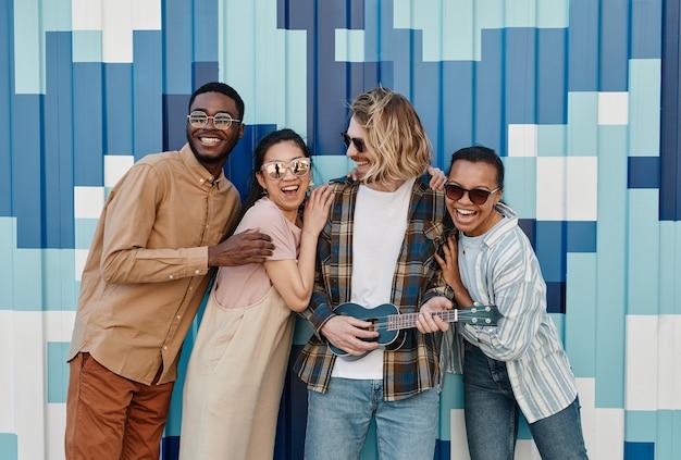 Diverse groep jongeren poseren buitenshuis door grafische muur in stedelijke stadsomgeving en glimlachen naar de camera