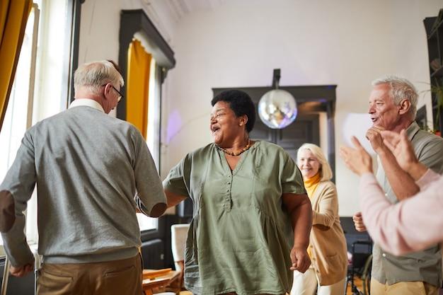 Diverse groep lachende senioren die dansen terwijl ze genieten van activiteiten in het bejaardentehuis, kopieer ruimte