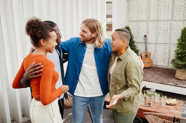 Diverse groep moderne jonge mensen die elkaar begroeten op een feestje op het dak, kopieer ruimte