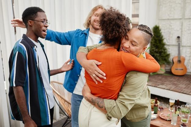 Diverse groep moderne jonge vrienden die elkaar begroeten op een feestje op het dak, kopieer ruimte