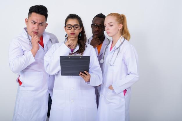 Diverse groep multi-etnische artsen die tijdens het lezen van een klembord denken