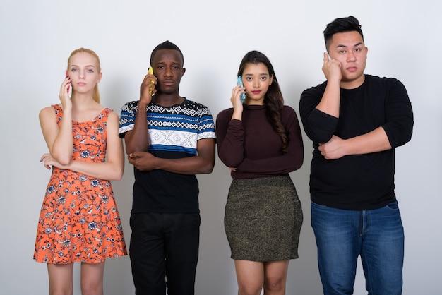 Diverse groep multi-etnische vrienden die op hun telefoons praten