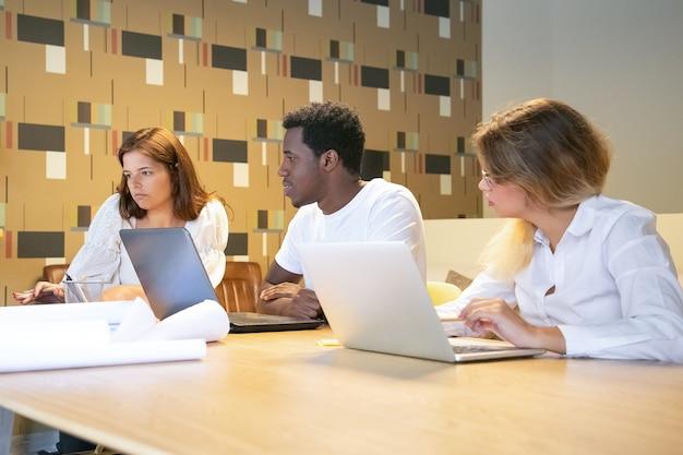 Diverse groep ontwerpers samen aan een project werken, aan tafel zitten met laptops en blauwdrukken en praten