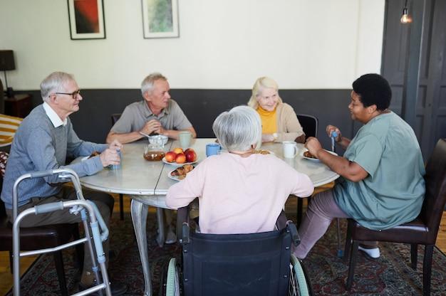 Diverse groep senioren aan het chatten aan de eettafel in het verpleeghuis
