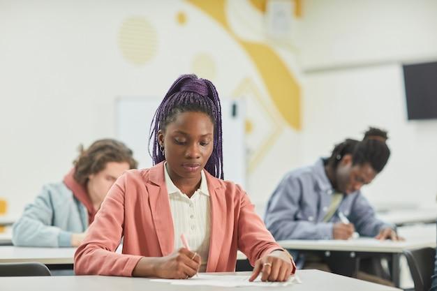 Diverse groep studenten die studeren in schoolklas met focus op jonge afro-amerikaanse vrouw die vooraan aan het bureau zit, kopieer ruimte