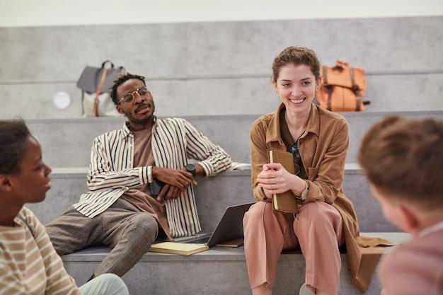 Diverse groep studenten vrolijk aan het kletsen terwijl ze ontspannen in de moderne schoollounge, focus op lachende jonge vrouw die met een vriend praat, kopieer ruimte